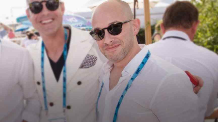Eyal Eran in white shirt and sunglasses smiling, more people in white shirts in the background