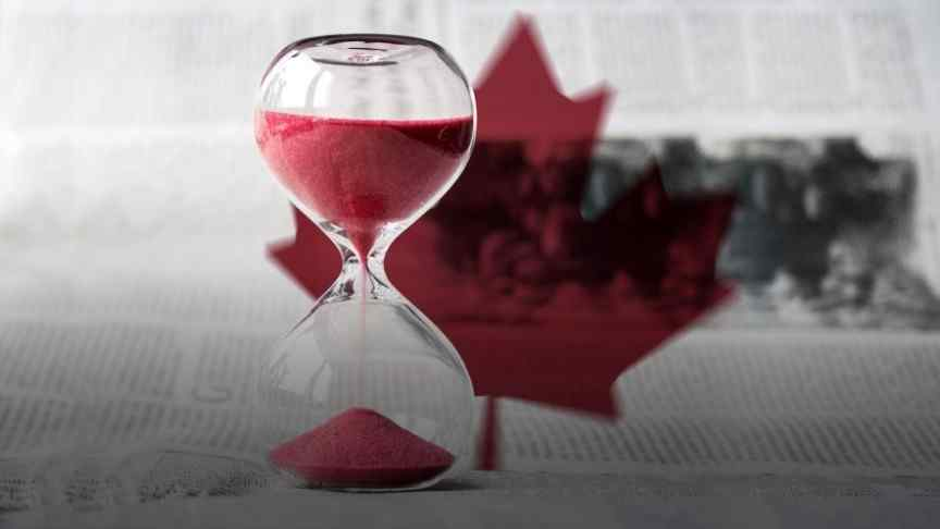 sand watch with red sand on background of newspaper with Canada's red maple leaf