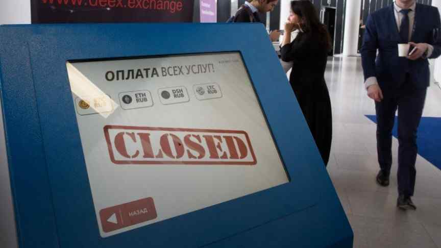 Blue Russian cryptocurrency ATM, screen shows CLOSED in red, business people walking in background