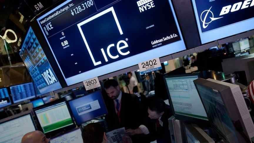 Intercontinental exchange room, people sitting at computers, big screens showing ICE