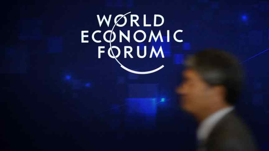 World Economic Forum logo, blurry man in suit, blue background
