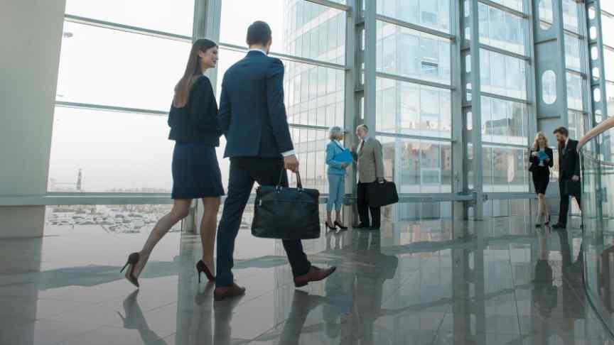 business people walking in a glass-door office