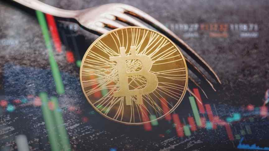 gold and see-through bitcoin and silver fork lying on carpet, blurry candle graphs in red and green