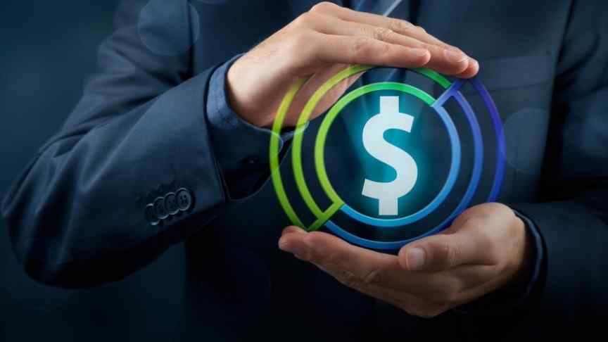 masculine hands in suit holding dollar sign in blue and green ring