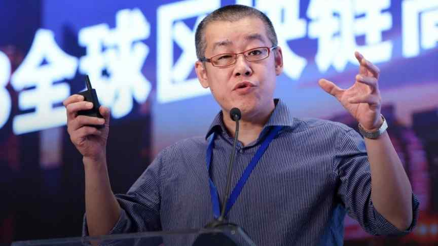 Li Xiaolai in grey shirt, raised hands, speaking into a microphone, chinese writing in the back