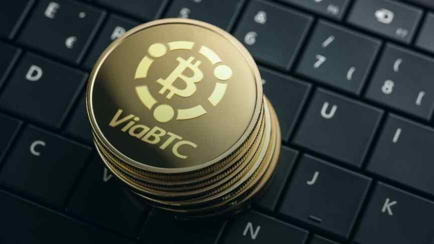 a stack of gold BiaBTC coins on a keyboard