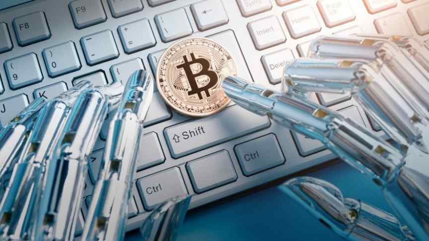gold bitcoin on white key board, silver robot fingers