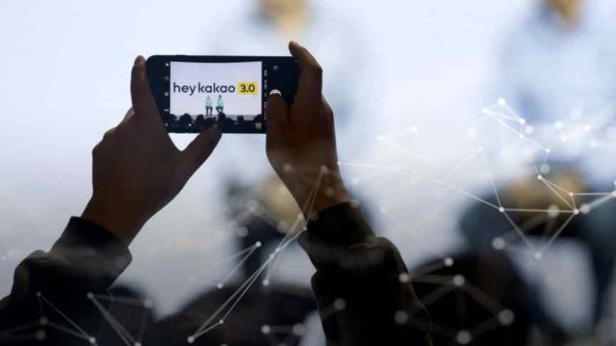 n/ahands holding smartphone, taking a picture of two people on a stage, caption 'hey kakao 3.0' above them