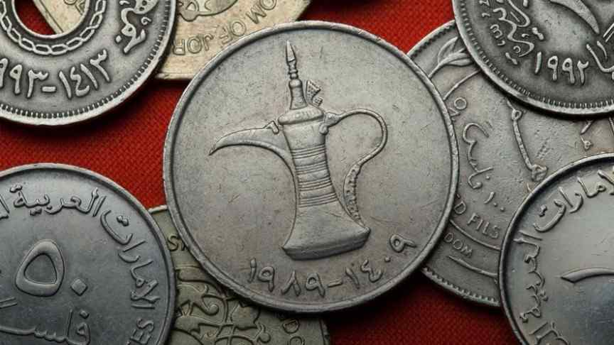 old silver coins with Arabic writings lying on red surface