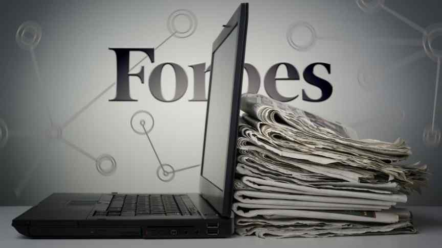 Forbes logo behind a desk with stacked newspapers and a laptop