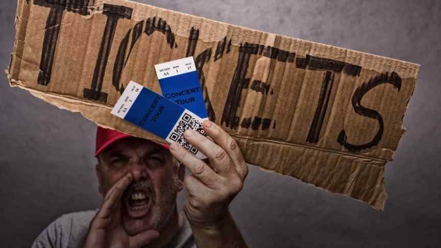 man in red hat shouting and holding cardboard sign saying TICKETS and two tickets