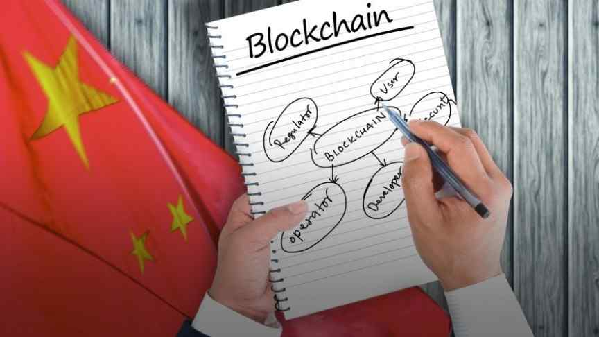 Chinese flag, wooden table, hand writing in notebook that says Blockchain
