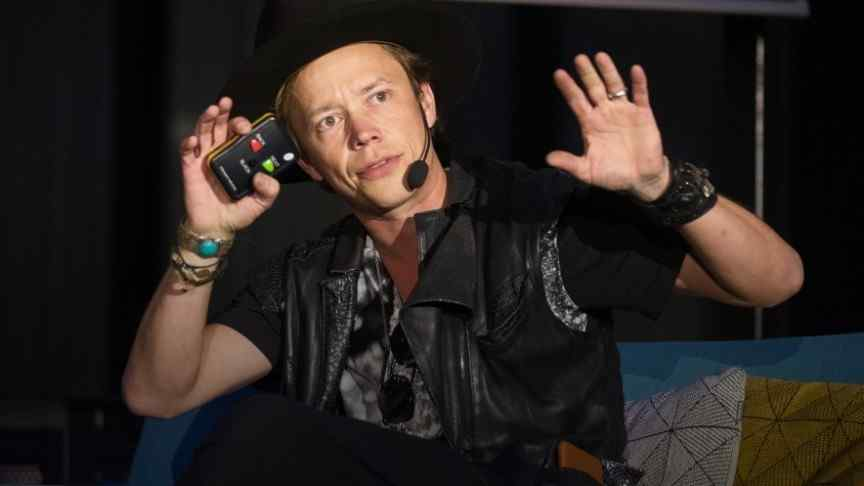 Brock Pierce holding arms up, holding phone, wearing ear piece