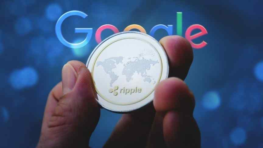hand holding coin showing map of world and Ripple logo, Google logo in the back
