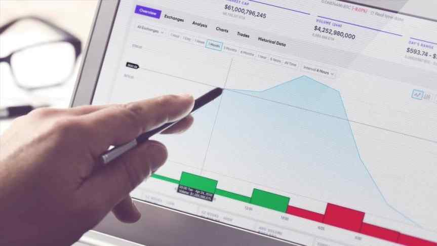 Hand holding a pen and pointing to a laptop display showing the ETH chart