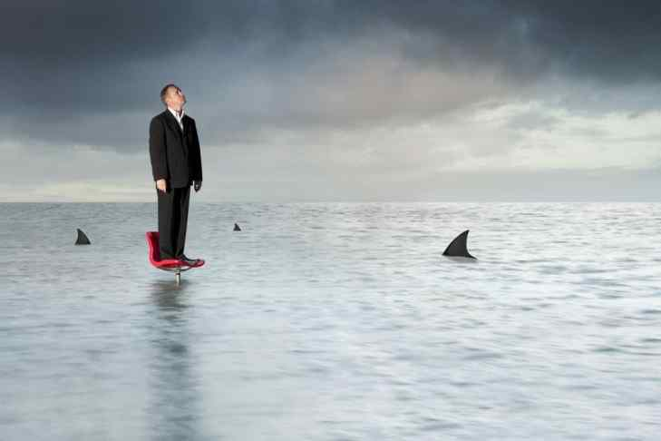 Suited man standing on a chair in the middle of the ocean, while sharks are near sighted