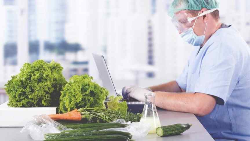 Doctor wearing a face mask and protection glasses sitting at a desk full of vegetables and operating a laptop