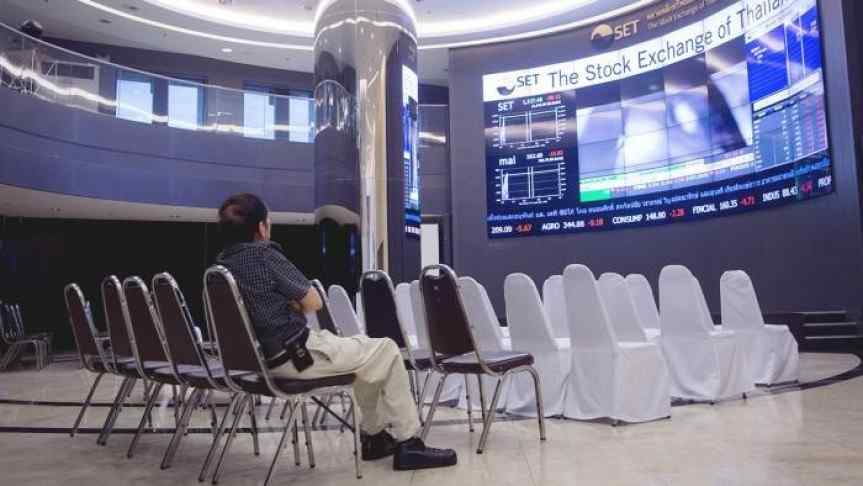 Man sitting in a conference room and watching The Stock Exchange evolution on a big screen