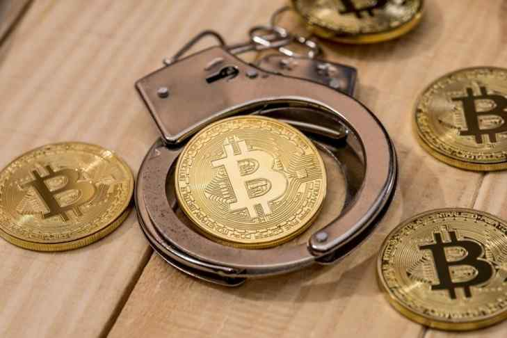 A couple of Bitcoins on a table and a pair of handcuffs