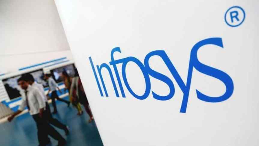 Workers passing by Infosys logo placed on a wall