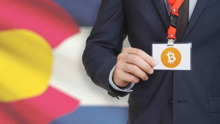 Suited man shoying his Bitcoin badge in front of the flag of the state Colorado