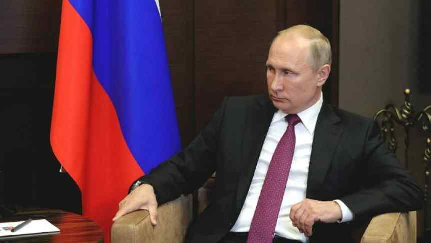 Vladimir Putin next to Russian Flag; contemplative look illustrating Russia's attitude toward cryptocurrency regulation.