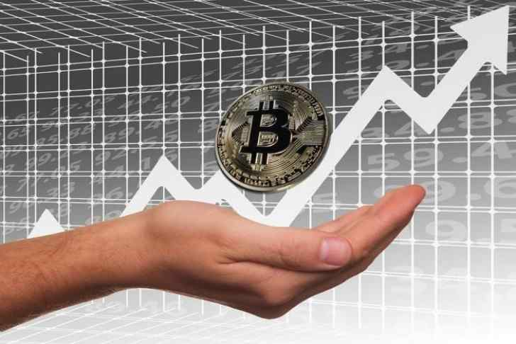 Hands showing a Bitcoin and an ascendant chart