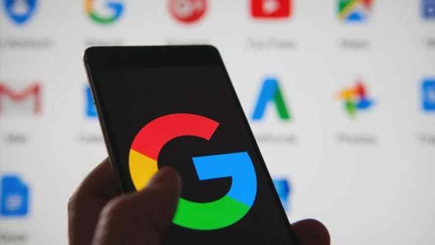 Google logo displayed on a phone, hold in front of a computer