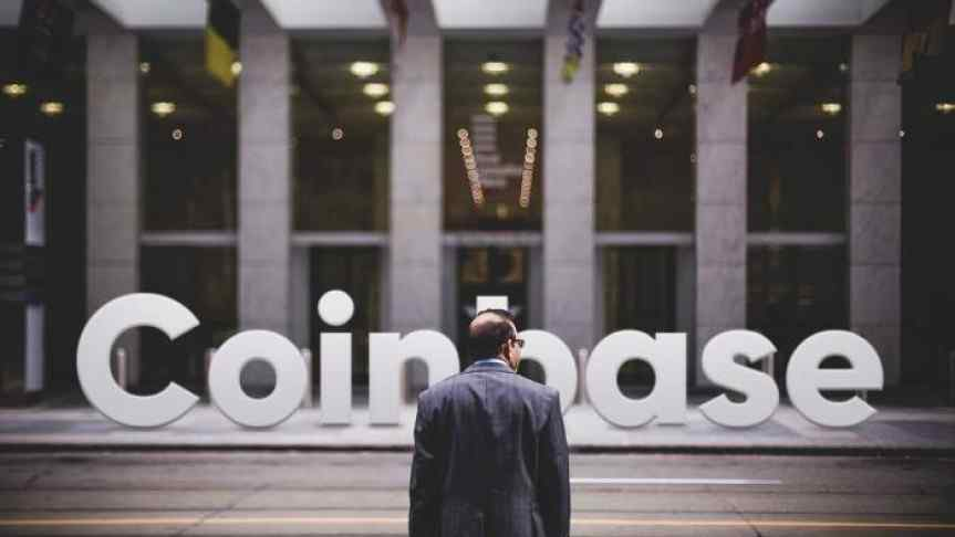 Man in front of a building and the Coinbase logo
