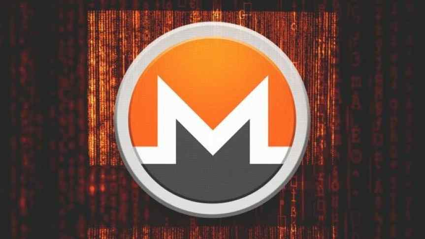 Monero enlarged logo on a stage, in front of red curtains.