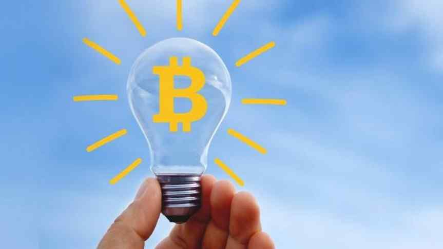 Lightbulb with Bitcoin sign on and drawn yellow sun rays around it; blue sky as background
