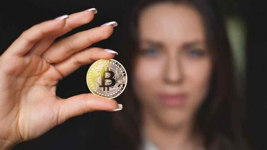 Picture of a woman showing a Bitcoin with the focus on the coin