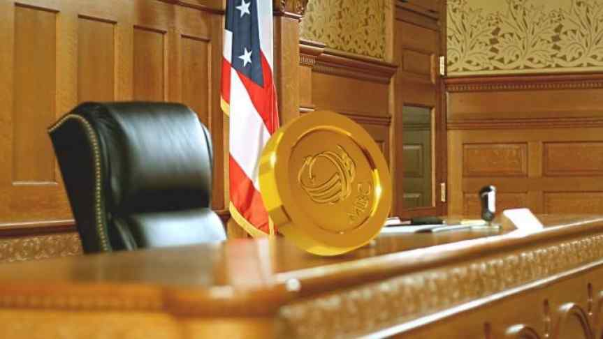 Bitcoin placed on counter of district courtroom, United States flag in background