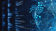 Iota logo and name in blue on background of screen with numbers and web