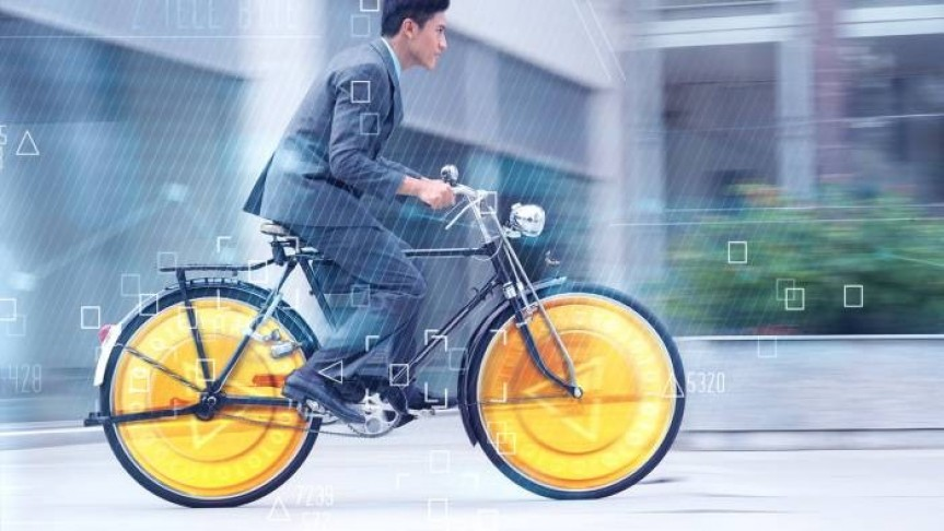 A man in suit riding a bicycle with yellow wheels., with triangles and squares floating in the air around him.