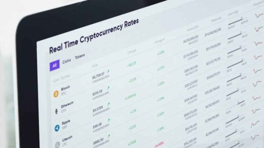 Bitrates real-time rates shown on laptop screen. Bitcoin, Ethereum, Ripple and Litecoin shown in green