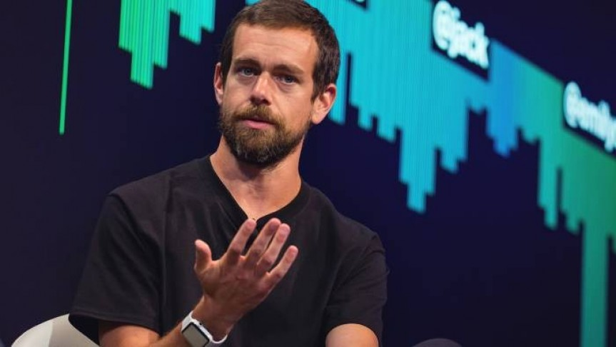 Jack Dorsey in black shirt with raised hand on background of black screen with green graph