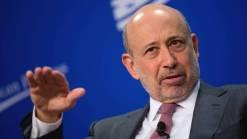 Goldman Sachs in suit, raising hand, blue background