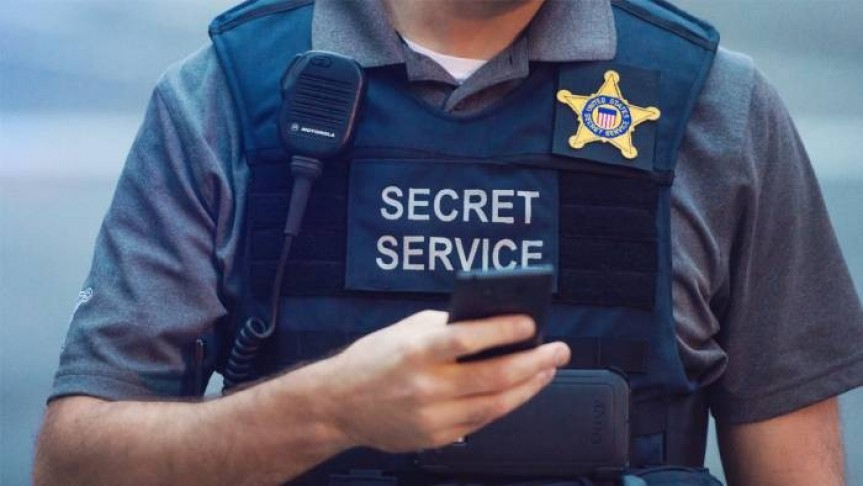 Man wearing grey shirt and Secret Service vest with radio and star logo, and holding phone in right hand.