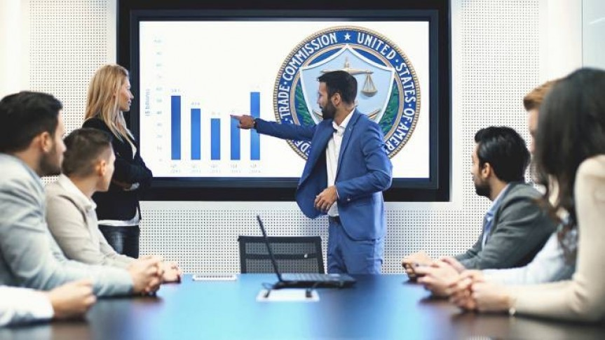 Man in blue suit pointing to graph and US FTC icon on screen in front of six people in suits sitting around office table.