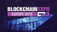 Sign: Blockchain written in white Expo written in Purple, Europe 2018 in white on purple bacground. In the Background lit conference room