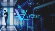VeChain name and logo in purple-blue. In the background man with glasses standing in storage room holding a computer.