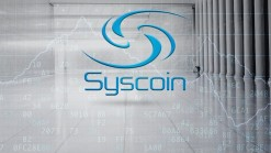 Syscoin name and logo in blue on grey background showing large foyer and market graph