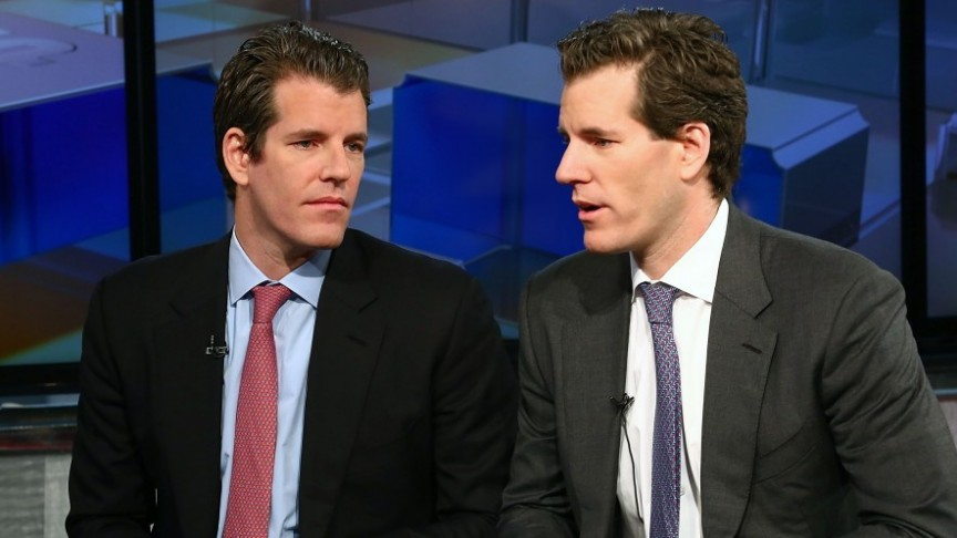 Winklevoss Twins sitting in an office. On the right in suit, blue shirt, red tie, black jacket. On the right, suit, white shirt, blue tie, grey jacket, mid speech