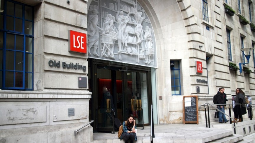 woman sitting on steps in front of LSE building, London