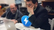Nick Spanos in black suit sitting in front of Apple lap top, Zap logo in blue