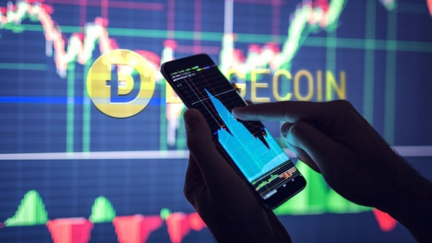 Dogecoin name and logo in yellow on background of screen showing graphs, hands holding smartphone also showing graphs