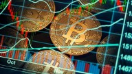Bitcoin gold coins seen on screen also showing graphs pointing up
