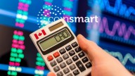 hand holding calculator that reads CAD and showing Canadian flag, in the background blurry graphs