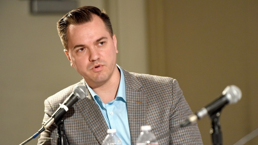 Austin Petersen in brown checkered jacket an dblue shirt, mid-speech, sitting next to two microphones
